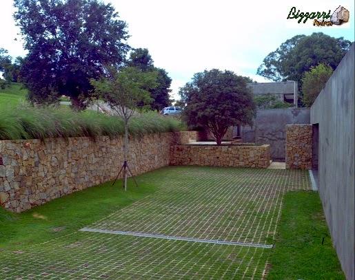Muro de arrimo com pedra madeira com vários patamares. Entre um muro de pedra e outro, nos patamares, plantamos as mudas de jaboticaba e no estacionamento o piso com concre-grama.