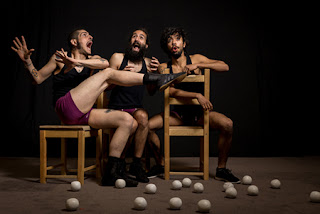 Three men sitting in chairs making funny faces and gestures