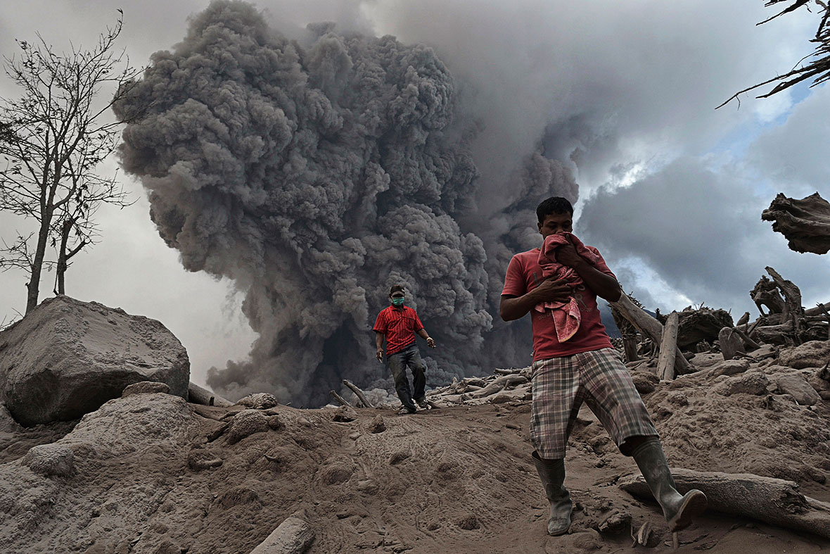 Villagers run on ash during the eruption of Mount Sinabung volcano near Gamber village in Karo district, on 21 January, 2014