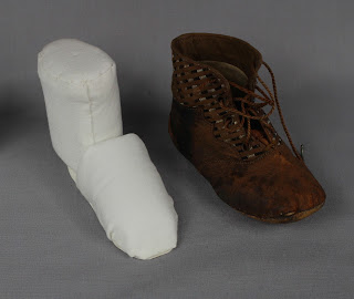 Storage and stabilization of a Child's 19th century leather boot artifact with custom made archival insert. Professional conservator Gwen Spicer is an expert in the care of textile, object and paper artifacts at Spicer Art Conservation in Upstate New York. Exhibit, storage and safe handling.
