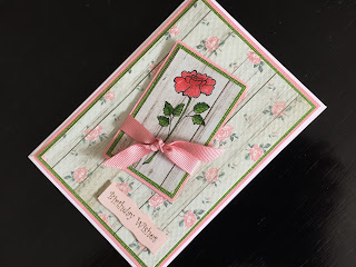Hand made birthday card with stamped rose on wood plank background paper