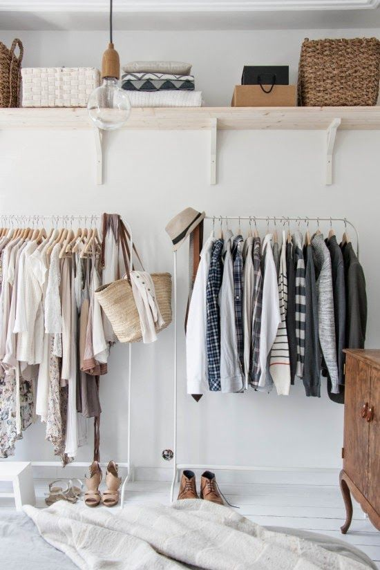 monochromatic clothes hanging in a steel rack in a clean and all white room