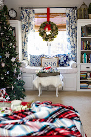 Blue and white master bedroom window seat with Christmas wreath and tree