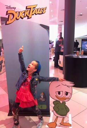 Girl poses in front of Disney Ducktales poster