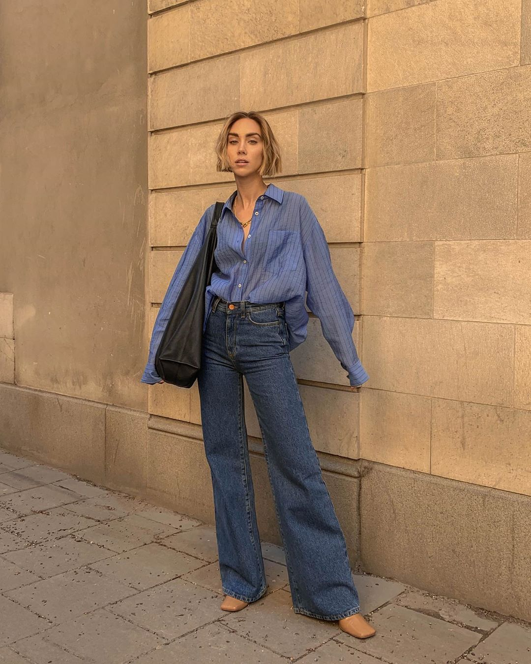 How to Wear Flared Jeans Like a Cool Scandi-Girl  — Lisa Olsson Instagram outfit with a blue button-down shirt, black tote bag, and square-toed shoes