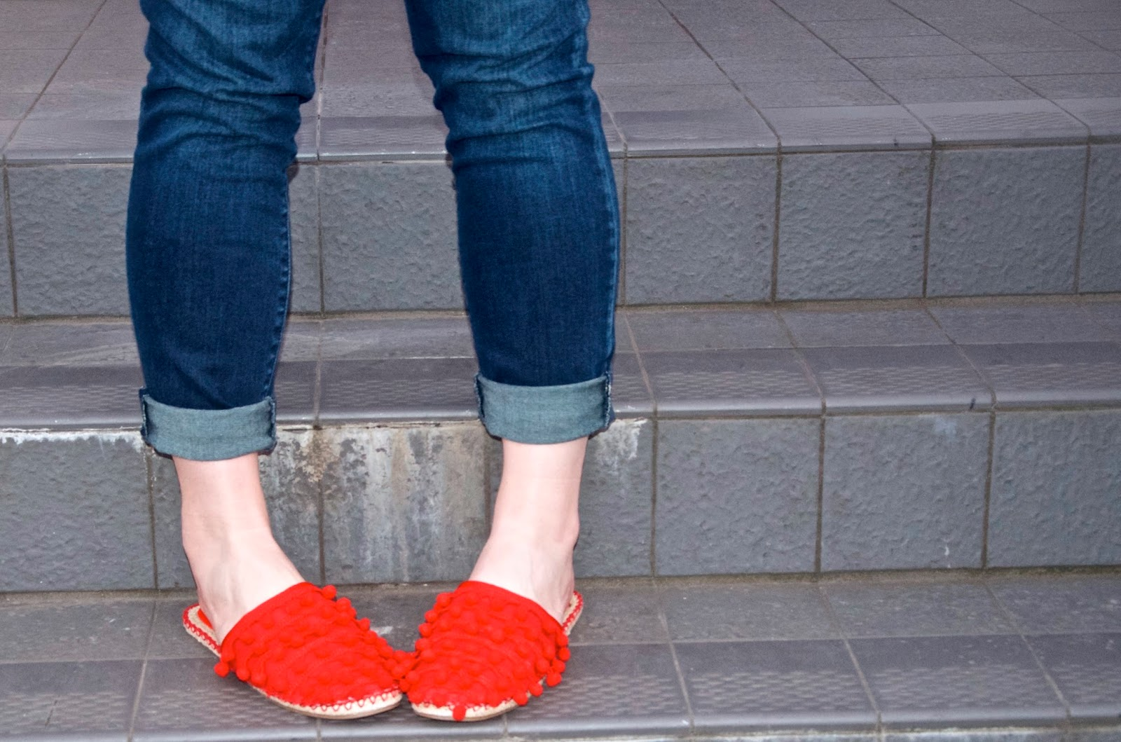 Red Pom Pom Mules and cuffed jeans
