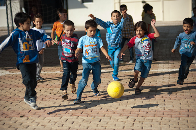 Meninos jogando futebol com bola no pátio da escola, amizade, conflito, briga, amigos, colegas, empatia, perspectiva