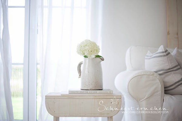 Gorgeous hydrangea in a vintage ceramic jug - Those floaty curtains are so pretty! bottle vases/demijohns and a stunning moroccan tray. I really love how the top of this little side table unit has been arranged and displayed! Glorious Shabby Chic Living Room Inspiration You Will Love!