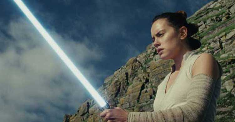 Daisy Ridley's Rey wields Luke's lightsaber in Star Wars: The Last Jedi.
