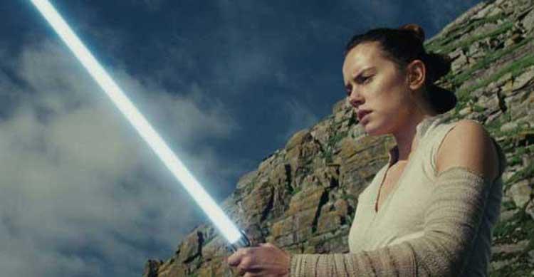 Daisy Ridley's Rey wields Luke's lightsaber in Star Wars: The Last Jedi.