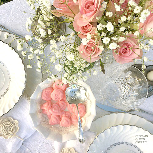 pink roses and baby breath centerpiece with white plates with silver rim and the sweet life engraved spoon.