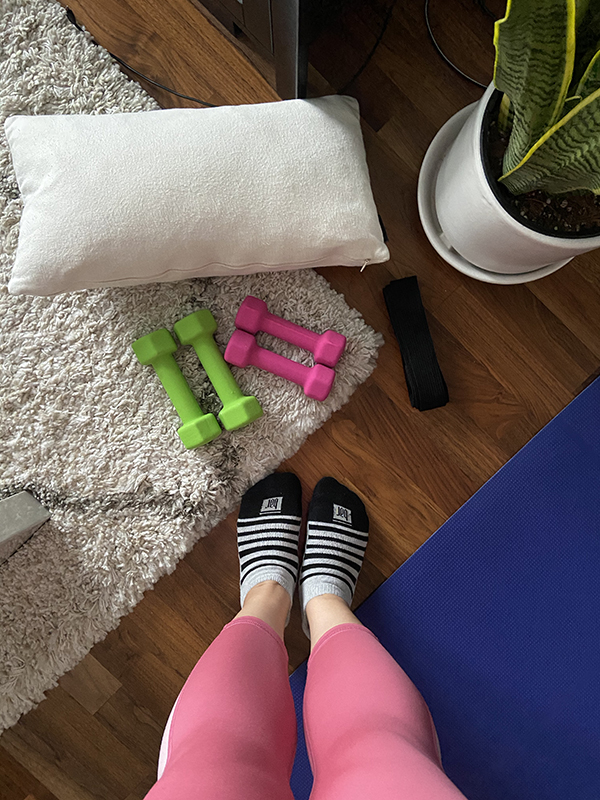 setting up for a Bar Method workout at home with light weights, yoga mat, stretching strap, and small pillow