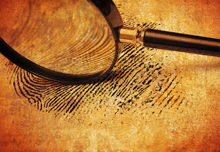 Photo of magnifying glass viewing fingerprint on old paper