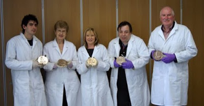 Some of the medal cleaning team showing holding cleaned Commemorative Penny from the First World War.  All wearing lab coats and gloves.