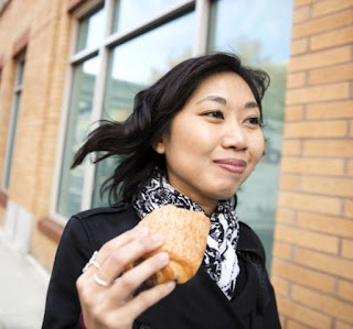 Photo of woman walking and enjoying pastry