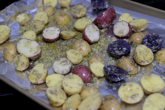 The seasoned raw potatoes on the foil lined baking sheet.