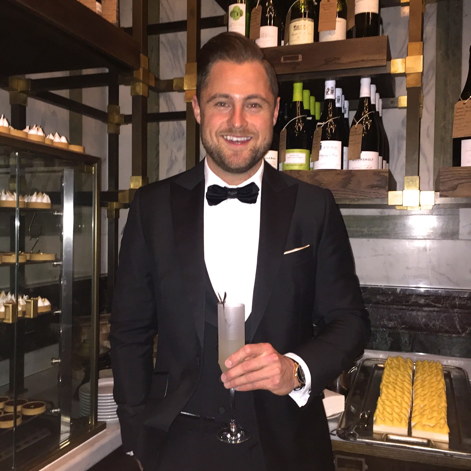 Man wearing Tuxedo and holding a cocktail at the BAFTA's Harvey Weinstein Afterparty 2016