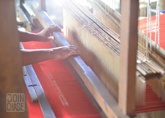 A woman's hands work the loom to make a red piece of fabric in Sagaing Division, Myanmar.
