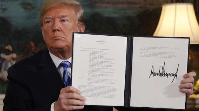 Trump displays a presidential memorandum after announcing his intent to withdraw from the deal