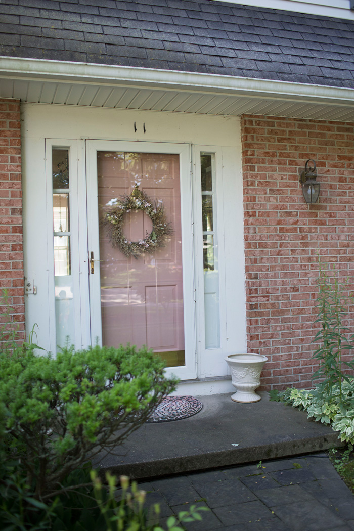 Colonial home with pink painted front door and brick exterior