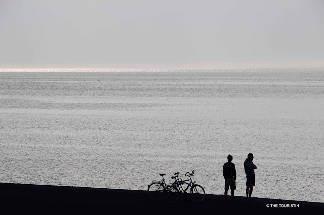 Two people standing next to their bikes looking over the glistening sea at twilight.