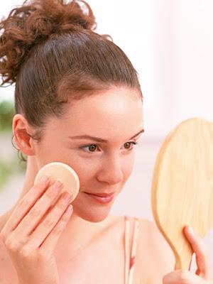Aplicándose base de maquillaje con esponja