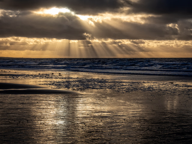 Photo of sun breaking through dark clouds over the Solway Firth in Cumbria, UK