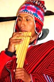 Foto de una persona con chullo y manta tocando la zampoña