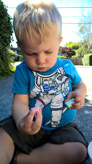 little boy in astronaut t-shirt playing with chalk in his driveway
