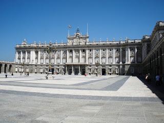 Una gran plaza se abre frente a la fachada sur del palacio, con arcadas a los lados.