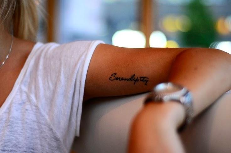 Chica sentada en jardin, lleva un tatuaje en el biceps de una frase que pone serendipiti