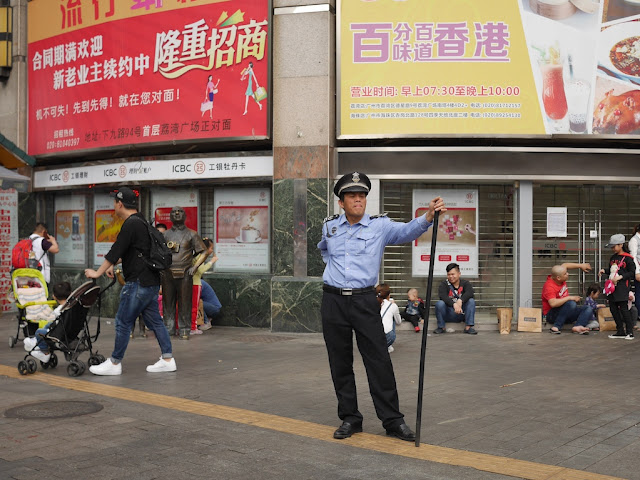 Shangxiajiu Pedestrian Street security guard standing with a large black staff