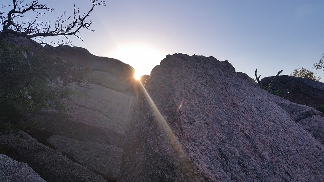 At the top of the granite dome at Enchanted Rock State Park, lies a boulder-strewn cave surrounded by small trees and shrubs.
