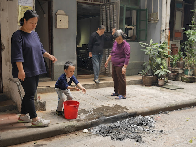 boy throwing water onto smoking ash
