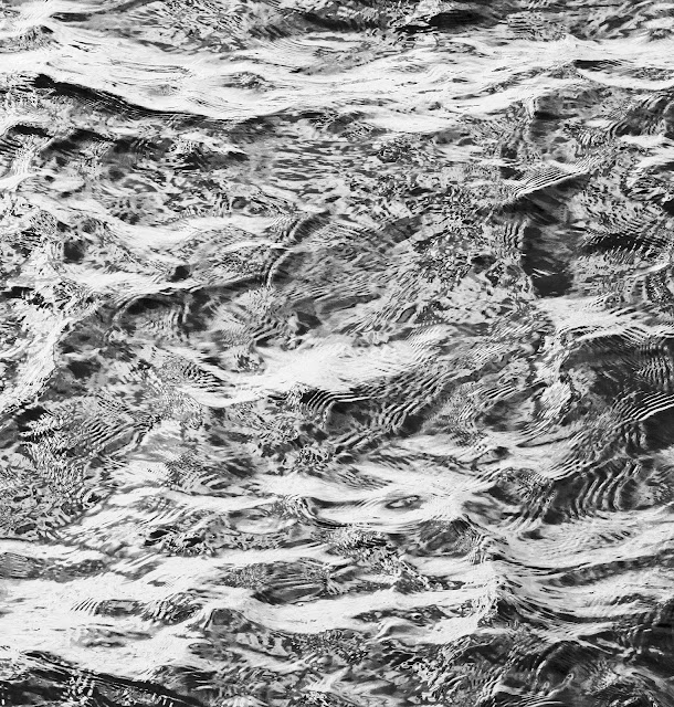 Monochrome of the sea where it hits rocks and returns against itself.
