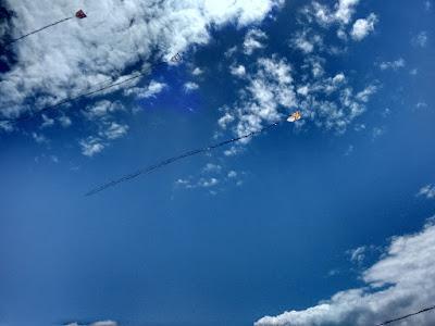 Fotografia colorida. Três pipas voando sob um céu azul com nuvens brancas.