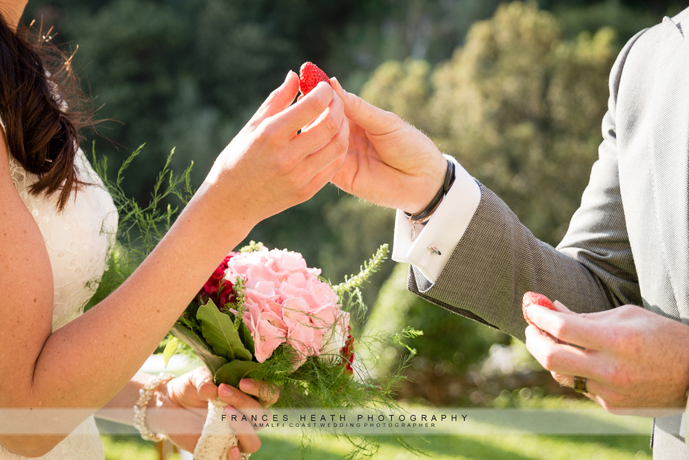 Bride and groom sharing a strawberry