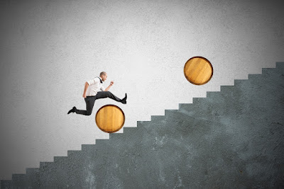 a business man is leaping over barrels as he tries to run up a staircase