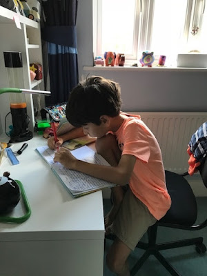 Small boy writing at his desk