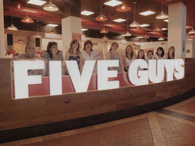 five-guys-lighted-sign-with-people-stood-behind