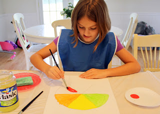 After tracing around a large bowl on watercolor paper and then dividing the subsequent circle into six parts with the aid of a ruler, Tessa used green, yellow, orange, red, purple and blue tempera paints to create a color wheel. She will use the color wheel to help her choose complementary colors in future lessons.