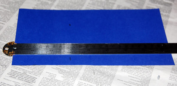 Blue scrapbook paper and pica ruler on newspaper