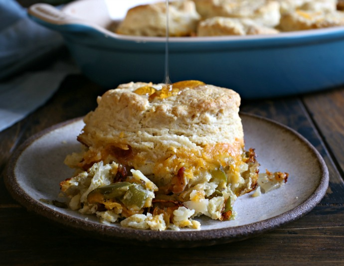 Recipe for a breakfast casserole with layers of potatoes, eggs, bacon and cheese, topped with biscuits.