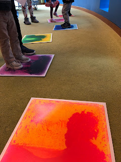 kids standing on colorful liquid tiles