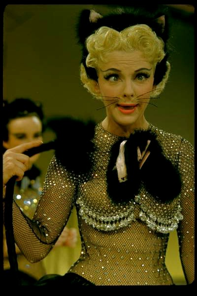 Photo of Vivian Blaine making goofy face in cat costume designed by Irene Sharaff for 1955 film Guys and Dolls