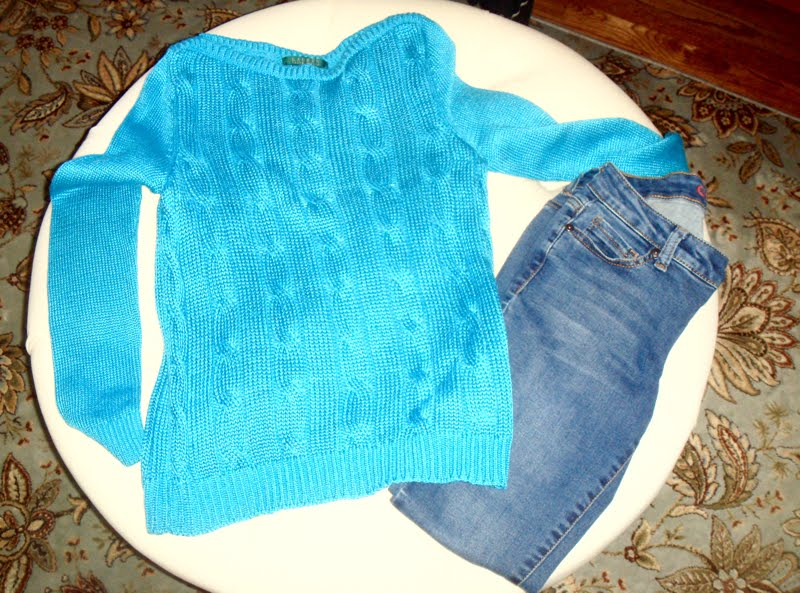 Blue sweater and jeans on ottoman.