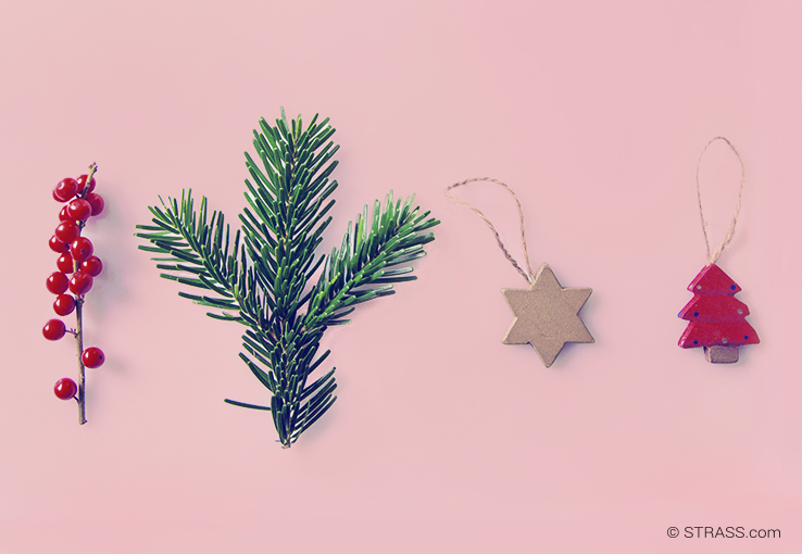 This picture shows different christmassy items layed on a pink background.