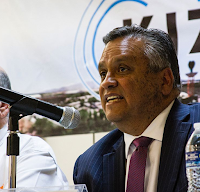 Photo of Chris Bustamante speaking in front of a microphone
