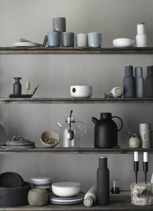 In einem Holzregal stehen Teller, Tassen, Karaffen und Kannen