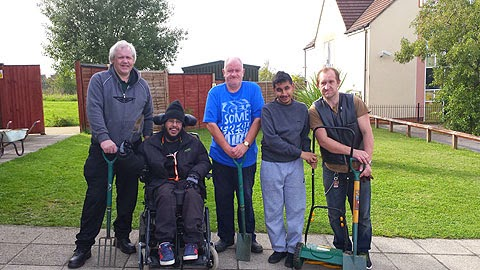 The Thurrock Lifestyle Solutions gardening group, posing with their gardening tools in front of All Saints Church in Chafford Hundred, Essex on a bright day.